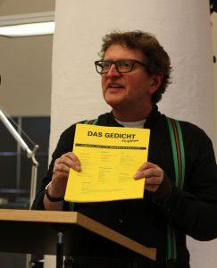 Anton G. Leitner, Herausgeber von DAS GEDICHT, präsentiert ein DAS GEDICHT-Flugblatt, Reminiszenz an »Der Zettel» und zugleich Werkzeug im Einsatz für Menschenrechte. Foto: Jan-Eike Hornauer